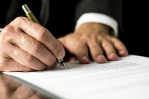 Close up of the hands of a businessman signing a typed document with a fountain pen with copyspace in the foreground.